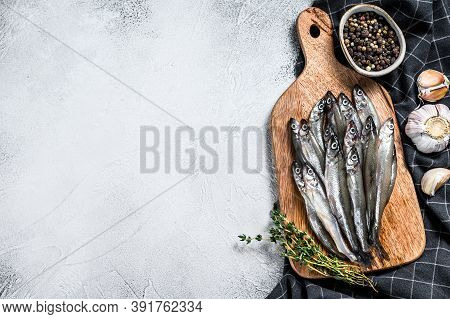 Raw Fresh Capelin Fish On Cutting Board. Gray Background. Top View. Copy Space