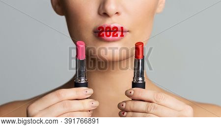 2021 Makeup Beauty Trends. Woman Choosing Lipstick Holding Cosmetics Near Face, With New Year Number