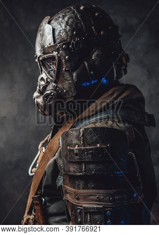 Profile Of Ragged And Futuristic Stalker With Dark Custom Armour And Gas Mask In Dark Background.