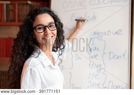 Education And Learning Concept. Portrait Of Smiling Female Teacher Standing At Whiteboard, Explainin