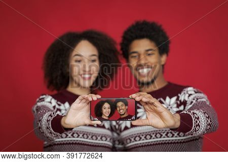 Family Photo On Holiday Of Christmas And New Year. Focus On Smartphone With Photo Of African America