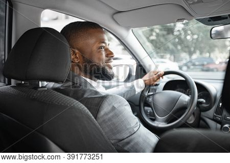 Cheerful African American Businessman In Silver Suit Driving Car, Shot From Behind. Happy Bearded Bl