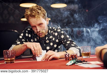 Elegant Young People Sits By Table And Playing Poker In Casino With Smoke In The Air.