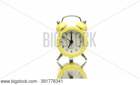 Small Yellow Old-fashioned Vintage Alarm Clock Rotating Isolated On White Background. Traditional Cl
