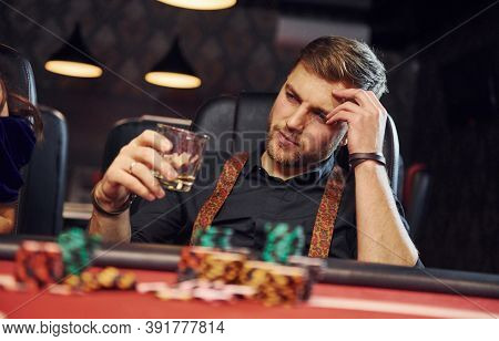 Elegant Young Man With Glass Of Alcohol Sits In Casino And Plays Poker Game.