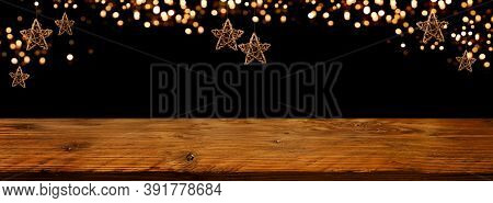 Golden Christmas Stars With Festive Bokeh Lights In Front Of Illuminated Rustic Wooden Table. Backgr