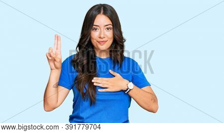 Beautiful brunette young woman wearing casual clothes smiling swearing with hand on chest and fingers up, making a loyalty promise oath