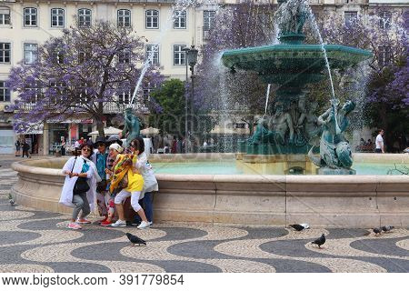 Lisbon, Portugal - June 4, 2018: Asian Female Tourist Group Take Selfie At Rossio Square Fountain In