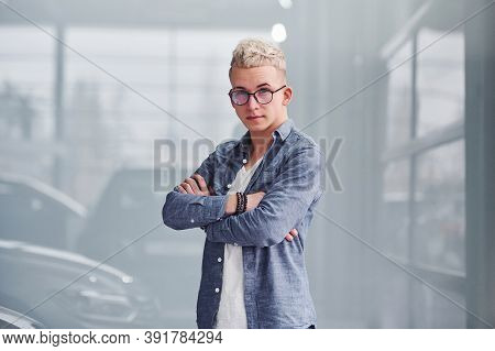 Young Hipster Guy In Nice Clothes Stands Indoors Against Grey Background.