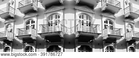 Detail of old balconies balcony on building with decorative windows and doors in apartment or hotel