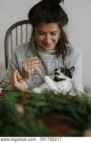 Cute Cat Helping Young Happy Woman Making Rustic Christmas Wreath. Pet And Holidays At Home