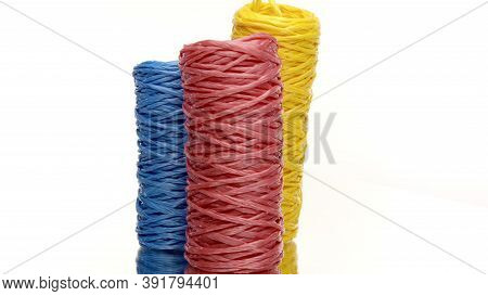 Three Skeins Of Colorful Recycled Plastic Twine Rotating On Isolated White Background. Hank Of Nylon