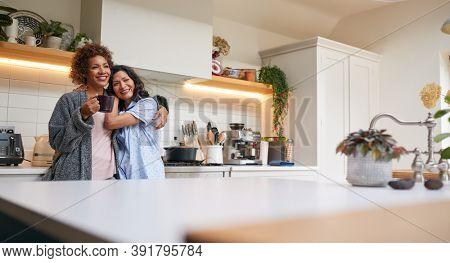 Loving Same Sex Mature Female Couple Wearing Pyjamas Hugging In Kitchen At Home Together