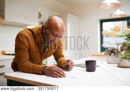 Mature Man Reviewing And Signing Domestic Finances And Investment Paperwork In Kitchen At Home