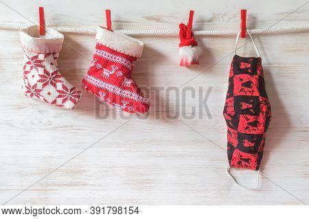 Safe Christmas Concept. Christmas Socks, Small Santa On Facemask Over White Wooden Wall. Christmas S
