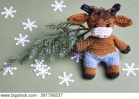 Knitted Toy Bull With Christmas Tree And Snowflakes On Green Background