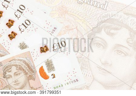 10 British Pounds Bills Lies In Stack On Background Of Big Semi-transparent Banknote. Abstract Busin