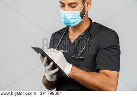 Indian Doctor Or Surgeon In Black Uniform With Stethoscope And White Latex Gloves, Blue Medical Mask