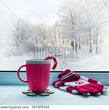 Winter Christmas background.Christmas still life.Christmas composition,red cup with candy cane on the windowsill and winter forest outdoors.Winter Christmas festive background,Christmas card,cozy Christmas stilll life