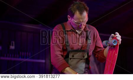 Caucasian Artisan In Overalls And Safety Glasses Repairs A Skateboard Or Pennyboard In His Workshop.