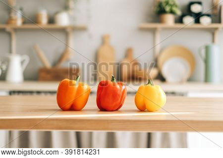 Colourful Sweet Pepper Paprika On The Wooden Table In The Modern Kitchen. High Quality Photo