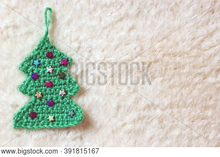 Green Christmas Tree Handmade Knitting With Beads On A White Background, Copy Space.  Do-it-yourself