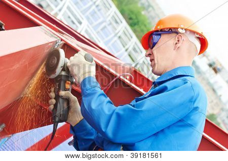 worker in safety protective equipment smoothing out welded joint at metal construction frame by angle grinder machine