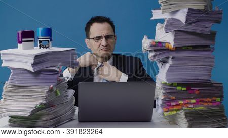 Overloaded Office Worker Working On Laptop Among Piles Of Paperwork And Stamps On Stack Of Documents