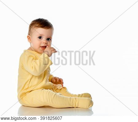 Little Baby Girl Wearing Yellowe Jumpsuit Scratching First Teeth Growing In Gum With Hand Finger Sit