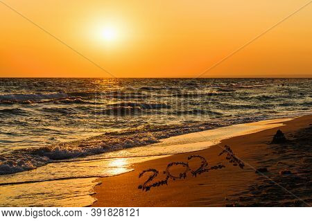 Inscription 2021 On The Seashore During Sunset. New Year And Christmas Concept. Beautiful Orange Sun