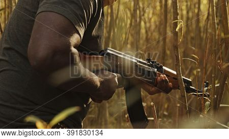 Close Up, Unrecognizable Black Man With Head Covering Pulling Triger Of Ak-47 Machine Gun. Concept O