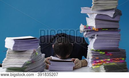 Stressed Businessman Accountant Manager Takes Stack Of Unfinished Documents From Large Pile Of Offic