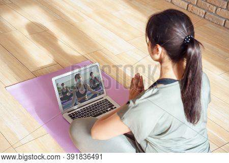 Young Woman Meditating Watching Live Online Tv Pilates Group Class Tutorial On Laptop Computer At Ho