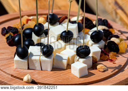 Close-up Compilation Of Snacks With Toothpicks On Wooded Plate.