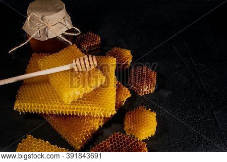 Honey Background. Natural Honey Comb And A Wooden Spoon . On Black Rustic Table.