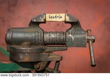 Concept Of Dealing With Problem. Vice Grip Tool Squeezing A Plank With The Word Lead-in