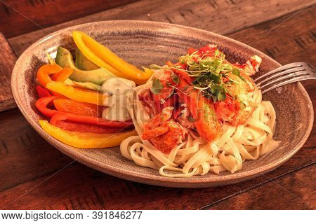 Maine Lobster Over A Bed Of Linguini With Micro Greens, Colorful Peppers And Avocado Sauce.