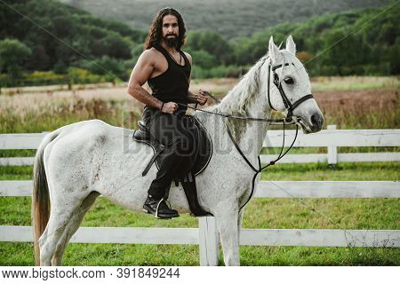 Man Riding Horse. Hunky Cowboy. Young Muscular Guy In T-shirt On Horseback. Sexy Male Torso