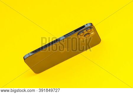 Paris, France - Oct 23, 2020: Yellow Background With New Iphone 12 Pro Max 5g Smartphone Model By Ap