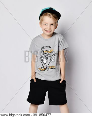 Cheerful Smiling Sporty Blond Kid Boy 6-7 Y.o. In Cap, Blue T-shirt With Dinosaur Eating Cars Print