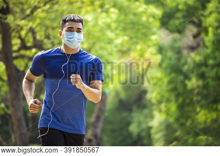 Man In Face Mask And Running In The Park