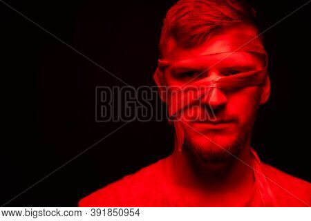 Low Key Portrait Of Bearded Young Bandaged Face Man Full-face Looking At Camera In Red Light On Blac