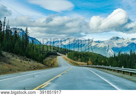 Rural Road In The Forest With Mountains In The Background. Alberta Highway 11 (david Thompson Hwy),