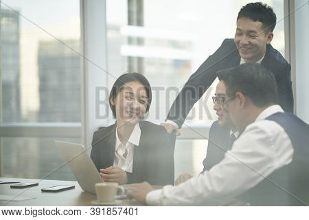 Through-the-glass Shot Of A Team Of Four Asian Corporate Executives Meeting In Office Discussing Bus