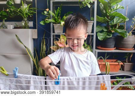 Cute Little Asian 4 Years Old Kid Having Fun Hanging Clean Washed Clothes On Drying Rack For Drying