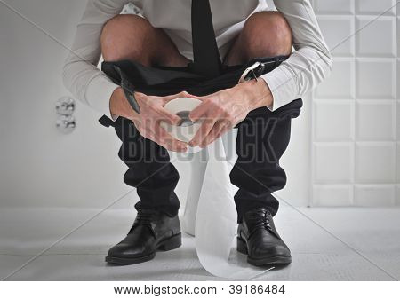 Young man in tie on a toilet holding a roll of toilet paper