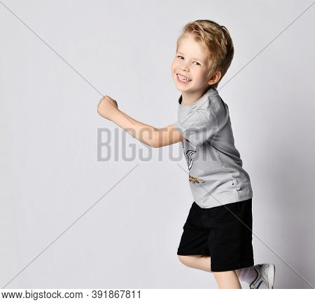 Portrait Of Cheerful Active Frolic Blond Kid 6-7 Y.o. Boy In Grey T-shirt With Print And Black Short
