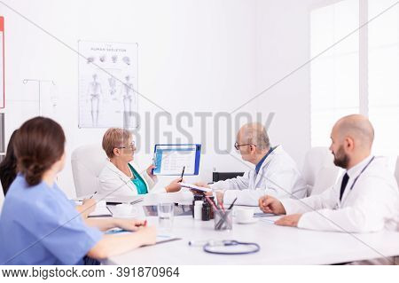 Experienced Doctors In Hospital Meeting Room Working Together During Health Seminar. Clinic Expert T