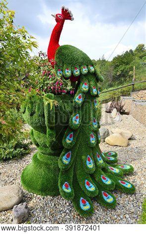 Novokuznetsk, Russia - August 15, 2020: Green Sculpture Of Peacock Created From Artificial Grass - G