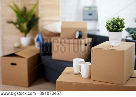 Moving Day Concept - Close Up Of Belongings Packed In Cardboard Boxes In Living Room